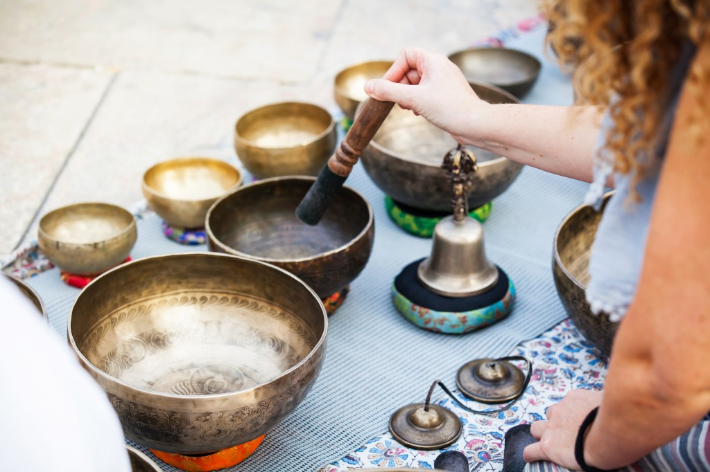 Hand playing tibetan bowls outdoors.